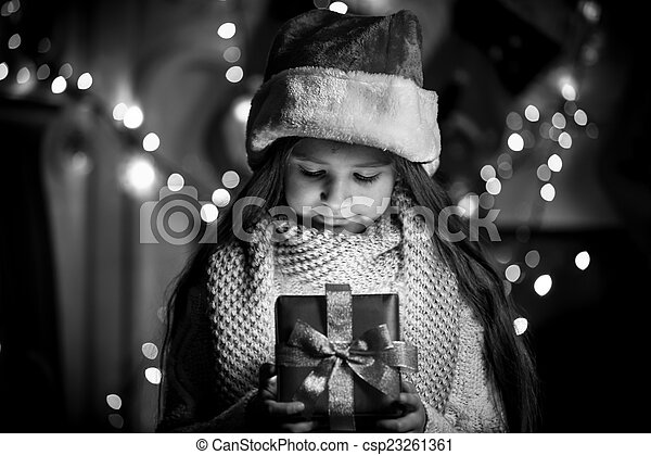 Monochrome portrait of smiling girl opening Christmas present bo
