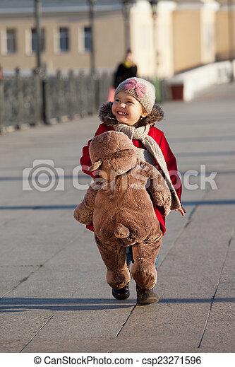 Little girl bears down the street a big toy bear