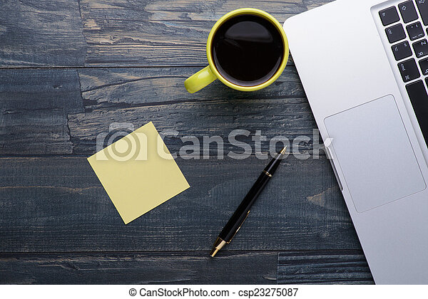 laptop with coffee, pen and notes on the wooden table