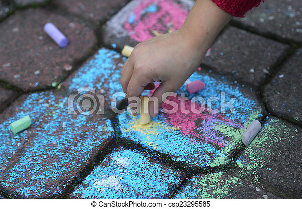 young girl draws with the colourful chalks on the road