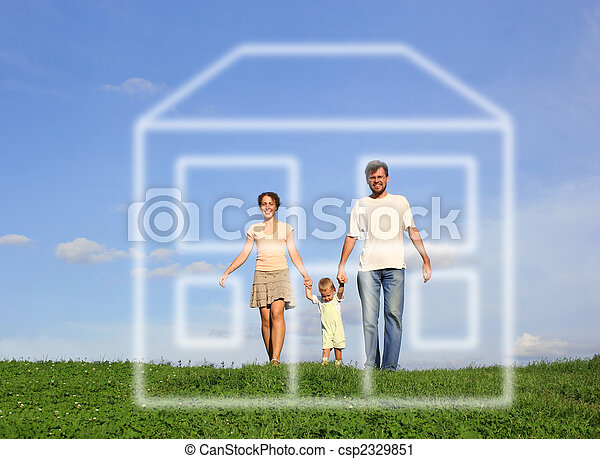 family with baby walking on grass and dream house