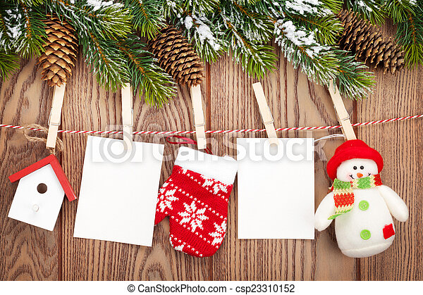 Snow fir tree, photo frames and christmas decor on rope over rus