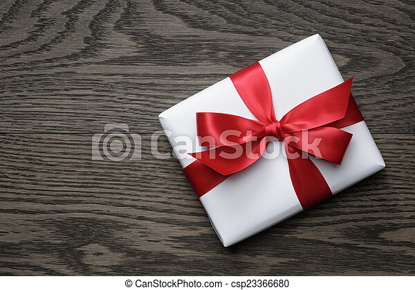 gift box with red bow on wood table