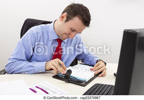 Happy entrepreneur consulting his agenda