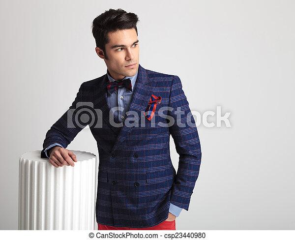 fashion man holding one arm on a white column.