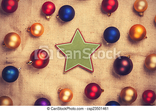 Star shape toy and color balls on jute background.