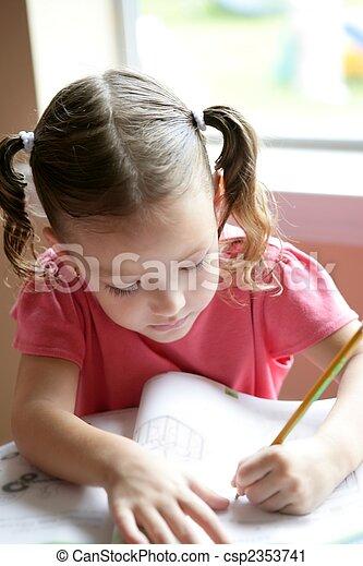 Little toddler girl writing at school desk, homework