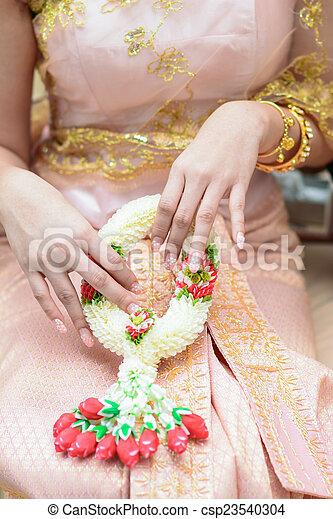 woman in beautiful thai dress hold thai garland