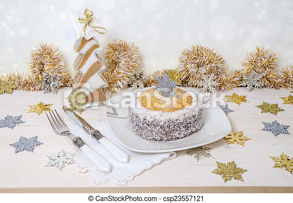 Festive pumpkin cake with coconut on table and Christmas decoration. Background bokeh