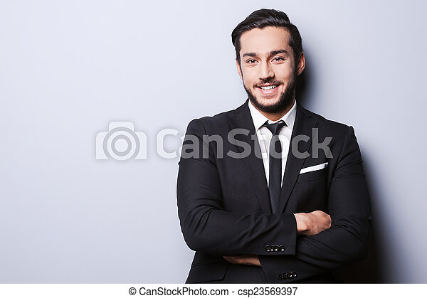 Successful businessman. Portrait of confident young man in formalwear looking at camera and smiling while keeping arms crossed and standing against grey background