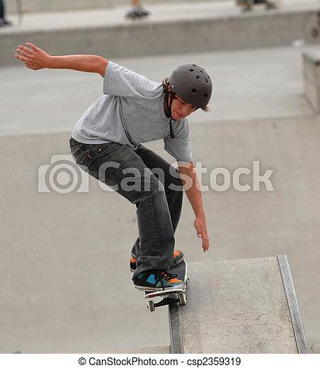 teenage skateboarder doing 50 50 grind on a rail - csp2359319