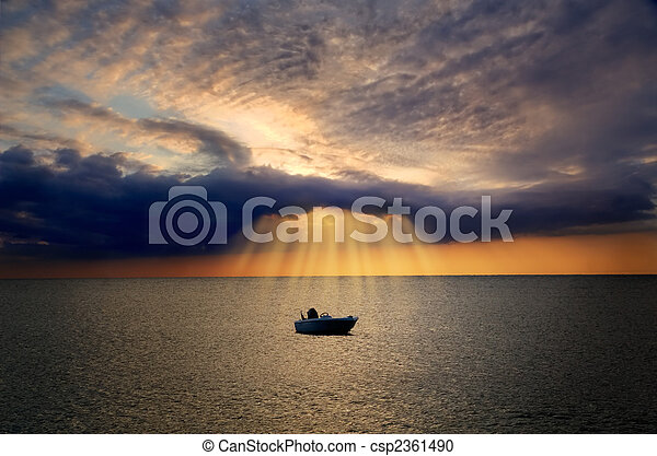 Lonely boat lit by divine light from cloud - csp2361490