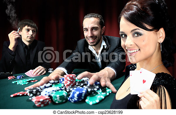 Poker players sitting around a table at a casino - csp23628199
