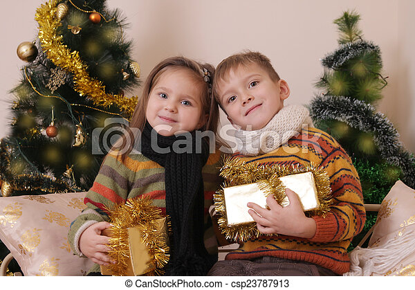 Sister and brother in knitted clothes with presents under golden