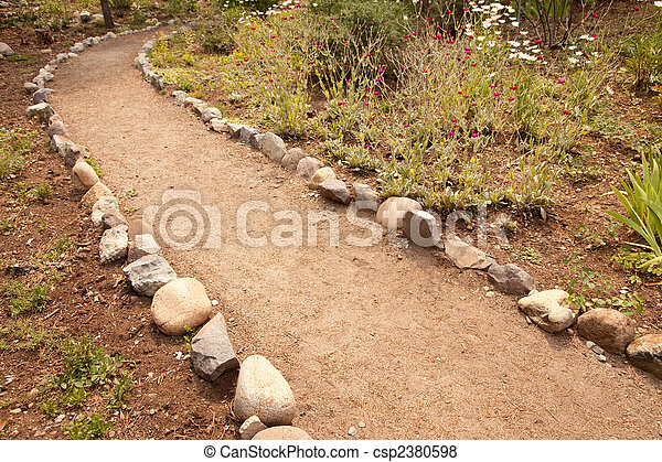 River Rock Lined Dirt Garden Path - csp2380598