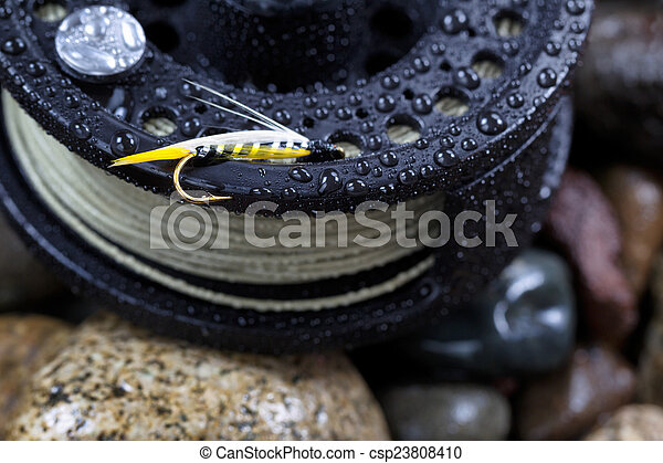 Close up of single trout fly, focus on golden barbed hook with shallow depth of field, on wet fishing reel with blurred out river rocks in background