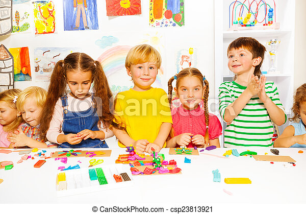 Happy boys and girls with plasticine in classroom