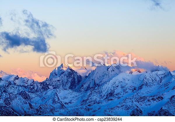 Mountain inspirational landscape beautiful sunset on Ushba, autumn or winter in Caucasus Mountains, Russia and Georgia. Mountain ridge over blue sunny sky, Russia