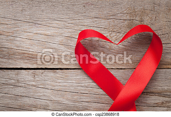 Valentines day heart shaped ribbon over wooden table background - csp23868918