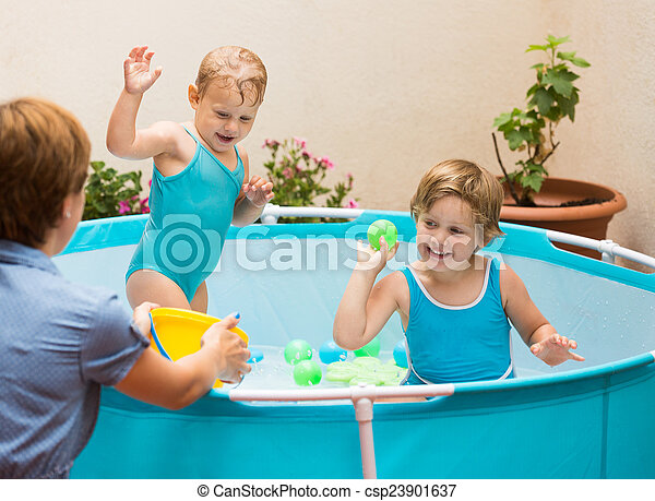 Children and mother playing in pool - csp23901637