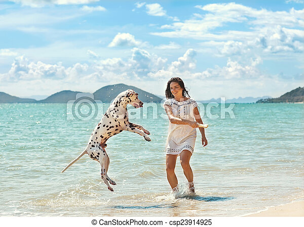 young girl with a dog walking on the sea