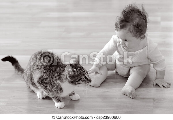 Baby (girl age 06 months) sits and plays with a pet animal (domestic cat) at home. Concept photo animals and children. (BW)