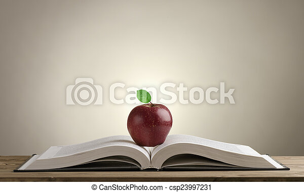 open book on a wooden Desk with a red Apple