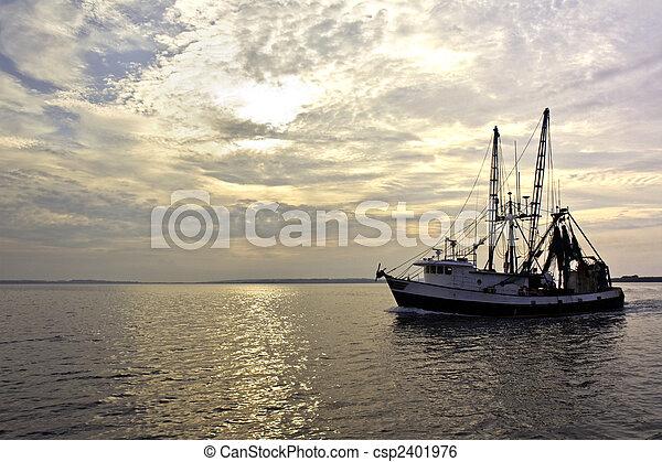 Fishing trawler on the water at sunrise - csp2401976