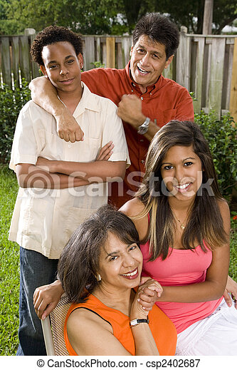 Interracial family relaxing in back yard - csp2402687