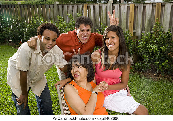 Interracial family relaxing in back yard - csp2402690