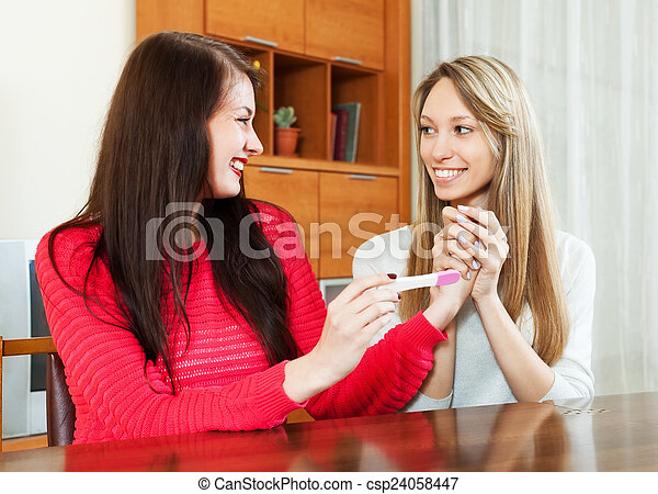 Happy girls looking at pregnancy test