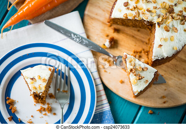 Carrot cake and cloth on table with fresh carrots