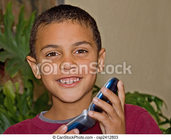 Cute 9 Year Old Bi-Racial Boy With Cell Phone - csp2412803