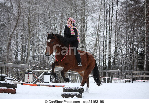 Teenager girl with brown horse show jumping without bridle and s