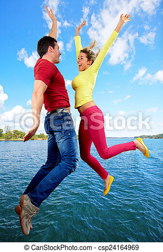 Happy people jumping over water
