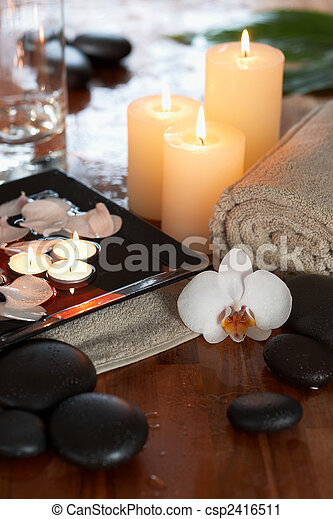relaxing spa with candles orchids towels and stones - csp2416511
