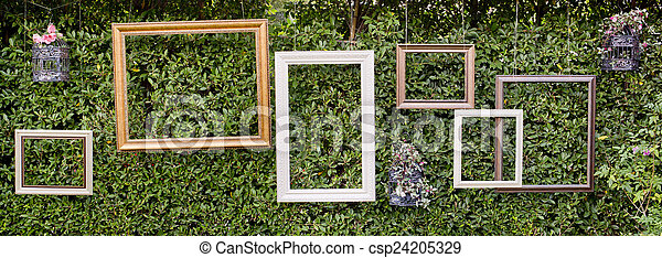 Blank photo frames against green small tree wall.