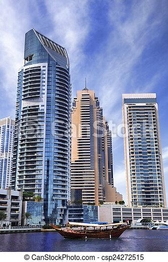 Dubai Marina with boats against skyscrapers in Dubai, United Arab Emirates