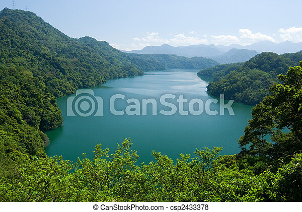 peaceful lake surround by forests and mountains - csp2433378