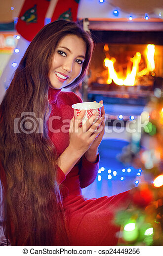 Beautiful smiling girl by the Christmas fireplace. Woman relaxes