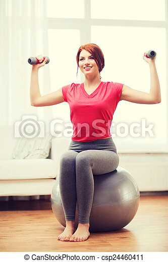 smiling redhead girl exercising with fitness ball