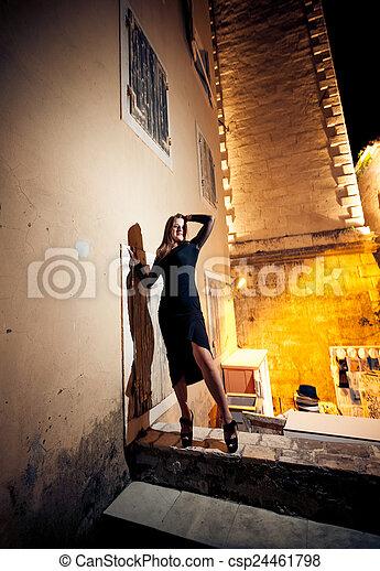 slim woman in black dress posing on street at night