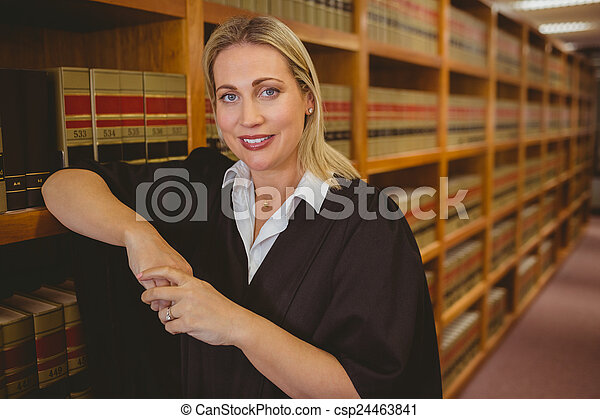 Smiling lawyer leaning on shelf - csp24463841