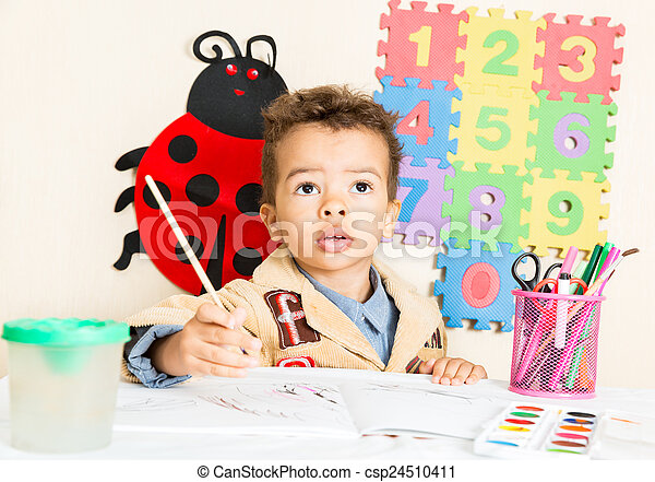 African American black boy drawing with colorful pencils in preschool at table in kindergarten