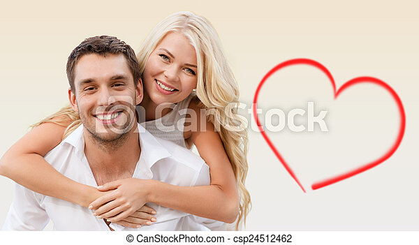 holiday, valentine\'s day, dating and love concept - happy couple having fun over beige background and red heart shape