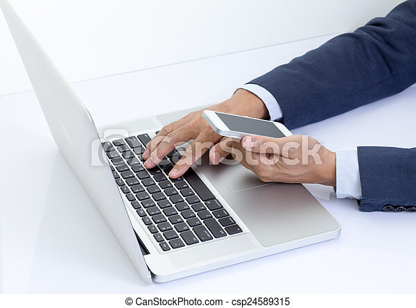 Businessman hand holding mobile phone with laptop computer