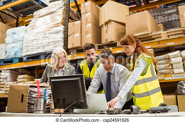 Warehouse managers and worker working on laptop - csp24591626