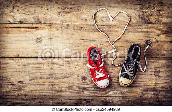 Original Valentine\'s Day love concept with red and black sneakers. Studio shot on a wooden floor background.