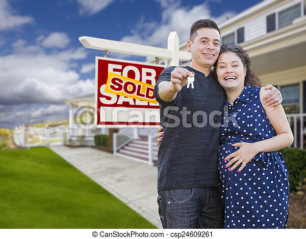 Hispanic Couple with Keys In Front of Home and Sign