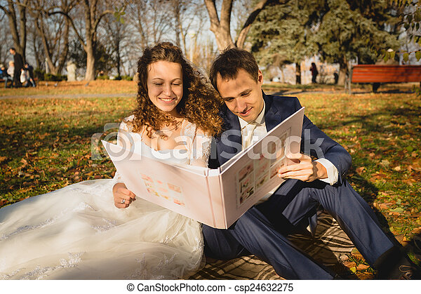just married couple sitting on grass at park and watching photos